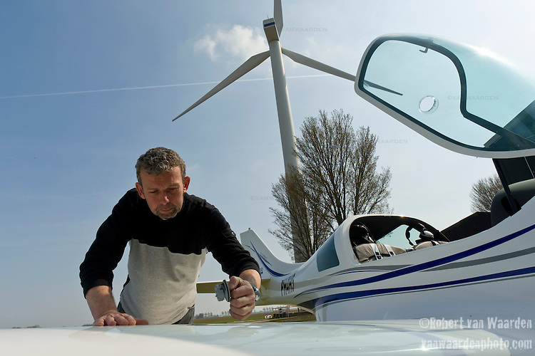 Jaap van der Beek checks the fuel of his airplane in Middenmeer, the Netherlands. Jaap van der Beek, pilot, wind farmer and farmer in Middenmeer, Holland. Mr. van der Beek owns one windmill on his property. Sensitive to recent decisions to try and group wind mills together from a government level, van der Beek is currently working with other wind mill owners in North Holland to secure a location for a collection of windmills. Until that time, van der Beek will continue to fly his plane and farm his tulips as the windmill powers him and hundreds of other homes.