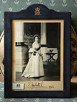 BNPS.co.uk (01202 558833)<br /> Pic: PhilYeomans/BNPS<br /> <br /> Signed portrait from the Queen.<br /> <br /> A remarkable 'timewarp' archive amassed by a dressmaker to the Queen has sold for over £100,000.<br /> <br /> The late Ian Thomas meticulously kept his fashion designs, letters, cards and photographs relating to the Queen at his home that was more like a museum. <br /> <br /> He helped design the Queen's coronation gown in 1953 as well as the powder blue outfit she wore for Charles and Diana's wedding in 1981.<br /> <br /> The lifelong bachelor passed away in 1993 and left his home and its contents to a florist he had been good friends with for 25 years.<br /> <br /> After she died in 2015 the property was inherited by a relative who also knew Mr Thomas well.<br /> <br /> She has now sold the contents at auction.