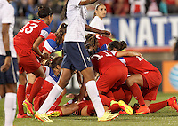 East Hartford, Connecticut - June 19, 2014: In an international friendly, United States Womens National Team (USWNT) (red/white/blue) tied France (white/blue), 2-2, at Rentschler Stadium. Alex Morgan at bottom of pile after scoring her second goal and second of the match.