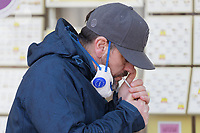 Pictured: A man removes his mask to light a cigarette in the city centre of Swansea, south Wales, UK. Friday 20 March 2020<br /> Re: Covid-19 Coronavirus pandemic, UK.