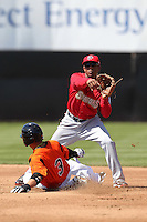 Harrisburg Senators shortstop Josh Johnson #15 attempts to turn a double play as Manny Machado #3 slides in during a game against the Bowie BaySox at Prince George's Stadium on April 8, 2012 in Bowie, Maryland.  Harrisburg defeated Bowie 5-2.  (Mike Janes/Four Seam Images)