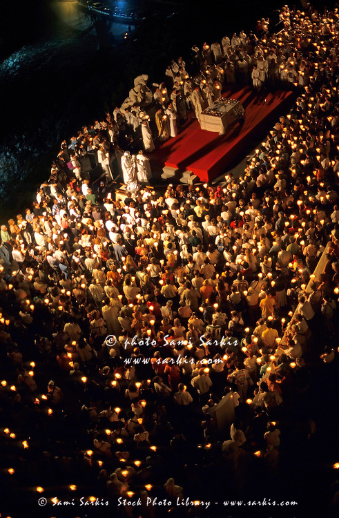 Crowd of people attending a candlelit mass on the day before the Assumption of Mary, outside Notre Dame de la Garde basilica, Marseille, France.