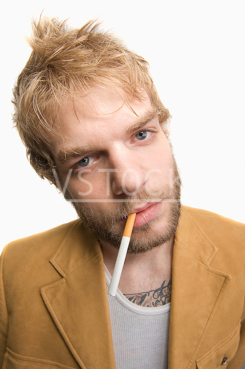 USA, Illinois, Peoria, Studio portrait of young man with cigarette in mouth
