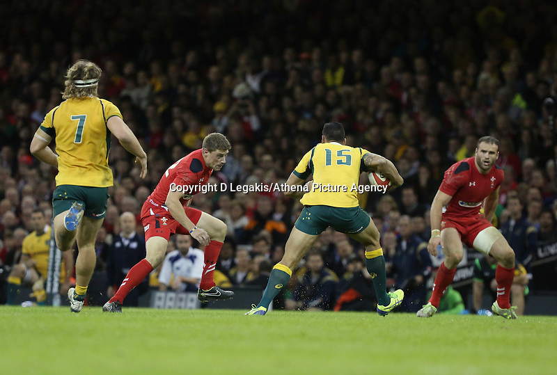 Pictured: Israel Folau of Australia (15) is closely watched by Rhys Priestland (2nd L) and Jamie Roberts (R) of Wales Saturday 08 November 2014<br /> Re: Dove Men Series rugby, Wales v Australia at the Millennium Stadium, Cardiff, south Wales, UK.