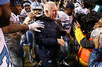 RALEIGH, NC - NOVEMBER 30: Head coach Mack Brown of the University of North Carolina is mobbed by his players at the end of the game during a game between North Carolina and North Carolina State at Carter-Finley Stadium on November 30, 2019 in Raleigh, North Carolina.