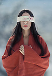 Artistic portrait of a beautiful asian woman with red sensual lips wearing a red undone kimono standing in the snow with a long black hair and a blindfold over her eyes Image © MaximImages, License at https://www.maximimages.com