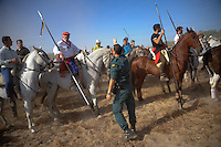 A Spanish civil guard gives instructions to men riding horses during the 'Toro de la Vega' festival, on September 11, 20112 in Tordesillas. The festival is one of the oldest in Spain with roots dating back to the fifteenth century. The bull has to be enticed across the river from the village to the plain 'Vega' before it can be killed to honour the 'Virgen de la Pena'. (c) Pedro ARMESTRE
