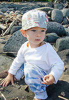 A young part-Asian local boy in a hat explores the black sand beach at Waipi'o Valley, Hamakua District, Big Island.