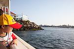 Asian boy in a baseball cap on the Aquabus crossing Rainbow Harbor in Long Beach, CA