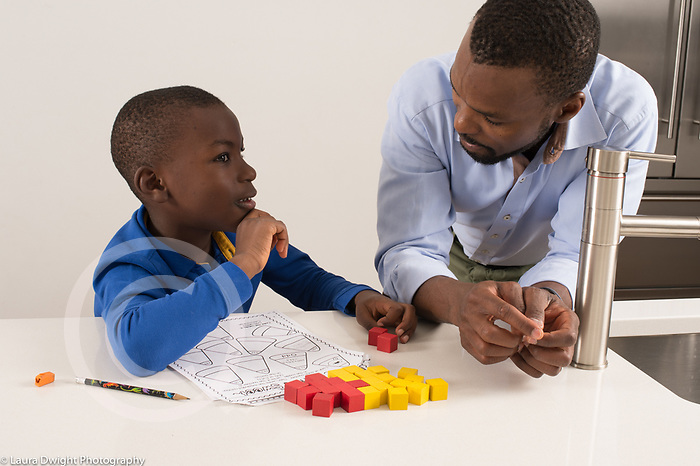 Seven year old boy at home, doing math assignment for homework, assisted by father, usng cube counters