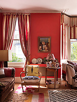 The delightful red-painted living room is complimented with red-striped curtains and pelmet and a variety of patterned rugs