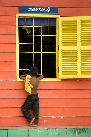 A boy peers through a window on the Vietnamese floating village near Siem Reap, Cambodia.  The Vietnamese floating villagers on branches of Lake Tonie Sap, Cambodia are a unique nomadic community. With permission from the Cambodian government, they have built an entire floating community of houseboats, churches, clinics, shops and community centers on the river near Siem Reap, Cambodia.  As the seasons change and the tides shift the entire village changes its location.  The villagers rely on sales of fruits and soft drinks to the many tourists who have come by boat to see firsthand the hardships of life on a floating village.