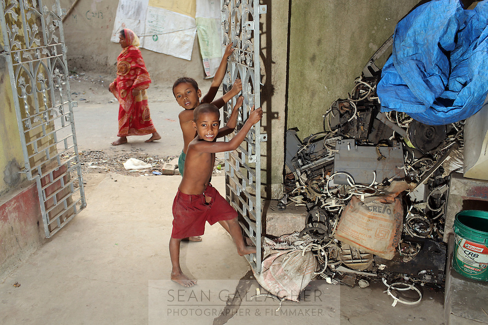 Children play barefoot near discarded piles of e-waste in the village of Sangrampur near Kolkata, India. November, 2013