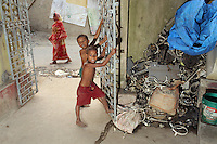 Children play barefoot near discarded piles of e-waste in the village of Sangrampur near Kolkata, India. November, 2013
