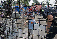 A Westerville, Ohio, police officer assists a youngster throw at the target of a dunk tank holding another police officer at the Cops and Kids Day at Hoff Woods Park in Westerville, Ohio.<br />