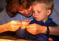 Child age 4 reluctantly accepting help from mother as she removes splinter.  Number 1 of a series of 2 images