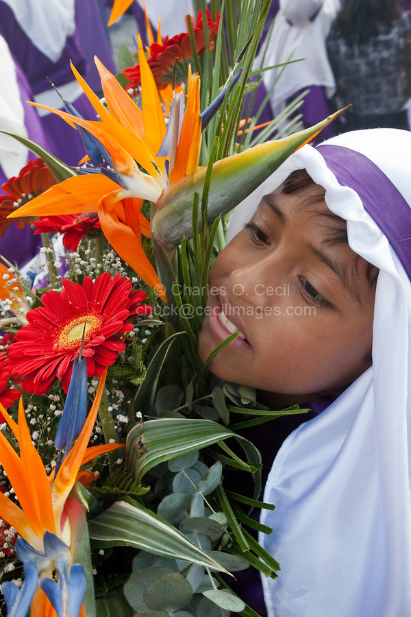 Antigua, Guatemala.  Young Cucurucho Carrying Large Vase of Flowers as he Accompanies a Procession during Holy Week, La Semana Santa