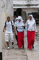 Zanzibar, Tanzania.  Adolescent Muslim Girls Wearing Head Scarves.  Young Man in Western Sporting Clothes.  Stone Town.