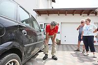 Bernd Petri (NABU Kreisvorsitzender) betrachtet die Schäden am Auto von Anja Runge