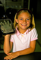 Smiling girl shows off hand-shaping discovery at science center