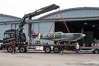 BNPS.co.uk (01202) 558833. <br /> Pic: CorinMesser/BNPS<br /> <br /> Pictured: Crews work to unload the Spitfire. <br /> <br /> A full-sized model Spitfire has been built as a memorial to the women and children who constructed over 2,000 of them in secret during World War Two.<br /> <br /> The crucial little-known operation involved just a few hundred people who operated in requisitioned car garages, sheds, workshops and factories in the city of Salisbury, Wilts.<br />  <br /> They had to sign of Official Secrets Act and worked with such discretion that the Wiltshire city's inhabitants were oblivious to it.<br /> <br /> They built the legendary aircraft in piecemeal, with the parts coming together to be assembled in one large factory that is now the local rugby club.