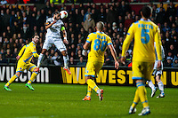 Swansea, UK. Thursday 20 February 2014<br /> Pictured: Ashley Williams ( with ball ) heads the ball forward for Swansea<br /> Re: UEFA Europa League, Swansea City FC v SSC Napoli at the Liberty Stadium, south Wales, UK