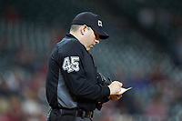 Home plate umpire Ryan Morehead updates his lineup card during the NCAA baseball game between the Arkansas Razorbacks and the Texas Longhorns in game six of the 2020 Shriners Hospitals for Children College Classic at Minute Maid Park on February 28, 2020 in Houston, Texas. The Longhorns defeated the Razorbacks 8-7. (Brian Westerholt/Four Seam Images)