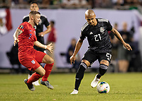 CHICAGO, IL - JULY 7: Luis Rodriguez #21 attempts to evade Paul Arriola #7 during a game between Mexico and USMNT at Soldiers Field on July 7, 2019 in Chicago, Illinois.