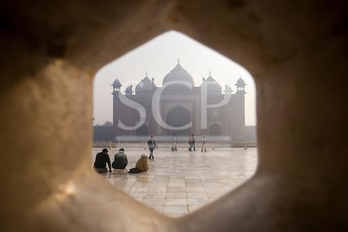 Agra, Uttar Pradesh, India. The Taj Mahal; main mausoleum; tourists and the Jawab building with its three domes outside seen through a lattice screen.