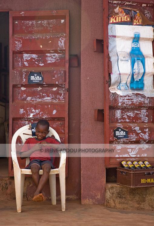 A boy lounges in front of a bar in Enugu, Nigeria.
