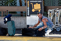 A Caucasian male traveler securing luggage, Honolulu International Airport, O'ahu