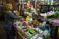Yogyakarta, Java, Indonesia.  Woman Examining Toiletries and personal care Items, Beringharjo Market.