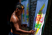 "A Colombian sign painter writes with a brush while working on music party posters in the sign painting workshop in Cartagena, Colombia, 17 April 2018. Hidden in the dark, narrow alleys of Bazurto market, a group of dozen young men gathered around José Corredor (""Runner""), the master painter, produce every day hundreds of hand-painted posters. Although the vast majority of the production is designed for a cheap visual promotion of popular Champeta music parties, held every weekend around the city, Runner and his apprentices also create other graphic design artworks, based on brush lettering technique. Using simple brushes and bright paints, the artisanal workshop keeps the traditional sign painting art alive."