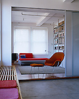 A rare Saarinen womb chair and ottoman and retro daybed furnish the cosy den which is separated from the dining room by sliding glass screens