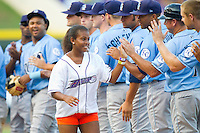"""Jourdan Blair receives high fives from the Wilmington Blue Rocks as she makes her way around the bases on her """"Home Run for Life"""" between innings of the Carolina League game against the Winston-Salem Dash at BB&T Ballpark on August 3, 2013 in Winston-Salem, North Carolina.  The Blue Rocks defeated the Dash 4-2.  (Brian Westerholt/Four Seam Images)"""