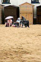 British seaside: holidaymakers sit on the beach in the rain