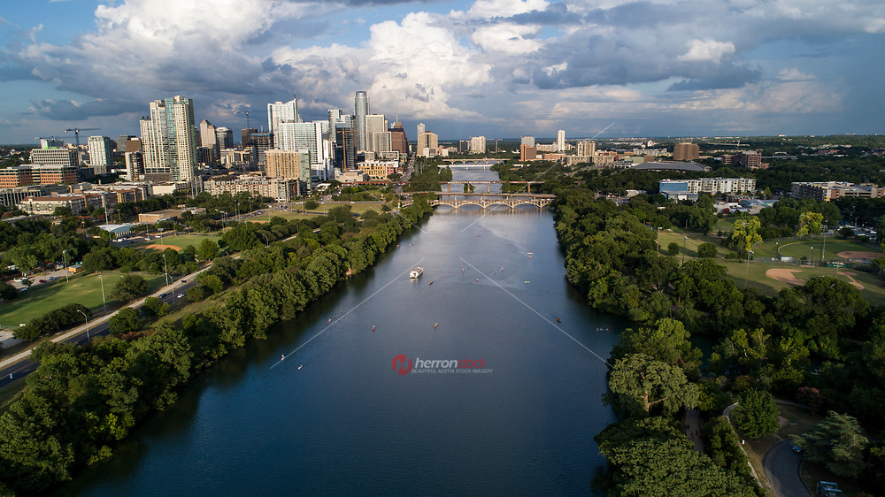 Beautiful aerial view looking east down Lady Bird Lake over the bridges connecting north and south Austin with the downtown cityscape during a cloudy summer's afternoon.