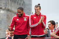 CARDIFF, UK. 8th July 2016. The Welsh football team are welcomed home with a public celebration event after reaching the semi-final of the Euro 2016 championship. After landing at Cardiff airport, an open-top bus parade took them through the city centre.<br /> <br /> L-R: Ashley Williams, Gareth Bale, Chris Coleman