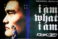 An elderly couple walks past a large Reebok advertisement featuring Yao Ming in Shanghai, China..