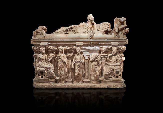 """Roman relief sculpted sarcophagus of Domitias Julianus and Domita Philiska depicted reclining on the lid, 2nd century AD, Perge. Antalya Archaeology Museum, Turkey.. Against a black background.<br /> <br /> it is from the group of tombs classified as. """"Columned Sarcophagi of Asia Minor"""". <br /> The lid of the sarcophagus is sculpted into the form of a """"Kline"""" style Roman couch on which lie Julianus &  Philiska. This type of Sarcophagus is also known as a Sydemara Type of Tomb."""