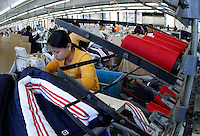 A young woman works at a sewing station at the Shengyuan Clothing Factory in Suzhou, Jiangsu Province, China. The factory employs a total of 250 workers that works year-round to fill clothing orders from Adidas and has expanded its operations to a more rural area of the province to meet the demand and cut down labor cost..16-OCT-04
