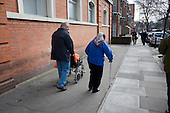 Elderly couple with a wheelchair and walking stick
