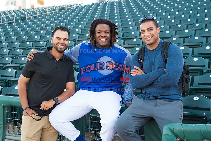 AFL West outfielder Vladimir Guerrero Jr. (27), of the Glendale Desert Dogs and Toronto Blue Jays organization, poses for a photo with coach Andy Fermin (left) and hitting coach Guillermo Martinez (right) before the Arizona Fall League Fall Stars game at Surprise Stadium on November 3, 2018 in Surprise, Arizona. The AFL West defeated the AFL East 7-6 . (Zachary Lucy/Four Seam Images)