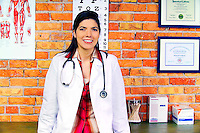 Female doctor in her office smiling with stethoscope and labcoat