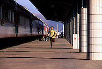 A boy runs on the platform at the train station, next to the from Beijing to Hong Kong long-distance train, Beijing, China.