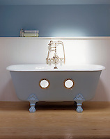 A blue free-standing bath with a roll top, claw and ball feet and two little portholes cut into the bath. The bath stands against a white panelled wall in a blue bathroom.