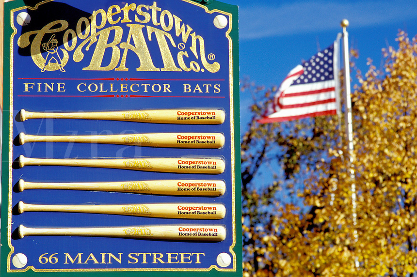 Cooperstown, New York, NY, Close-up of sign at Cooperstown Bat Company in downtown Cooperstown. Home of Baseball. American flag flies in the background.