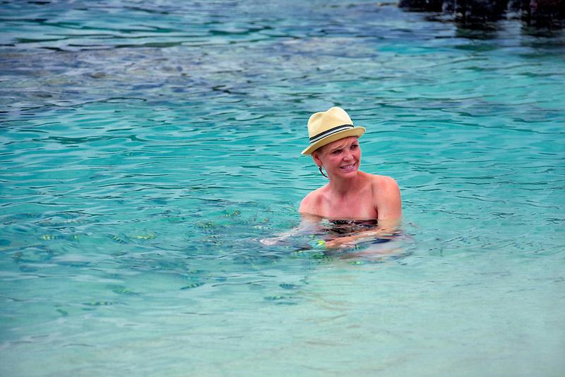 Swimmer feeding tropical fish at Coki Beach. St. Thomas. US Virgin Islands.