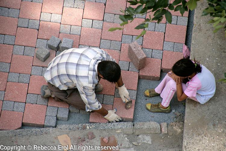 Turkish builder sets granite paving stones in road, Istanbul, Turkey