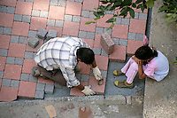 Turkish builder sets granite paving stones in road, Istanbul, Turkey